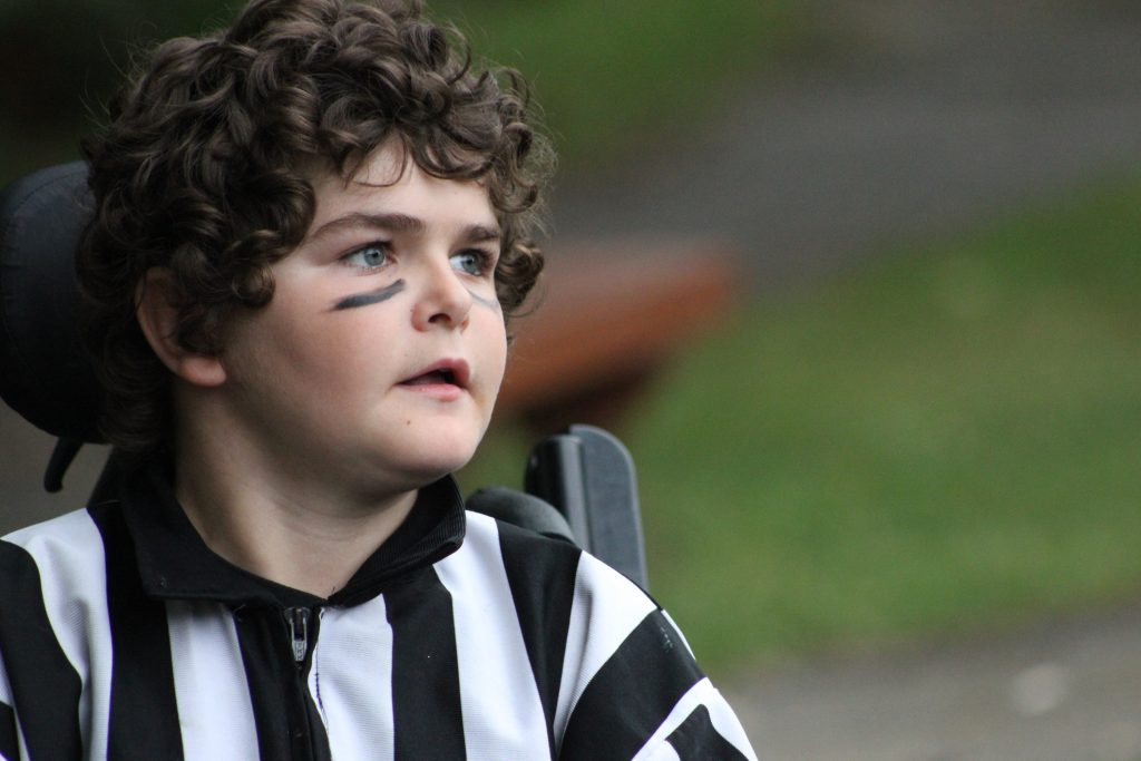 Young boy dressed as a referee in his wheelchair